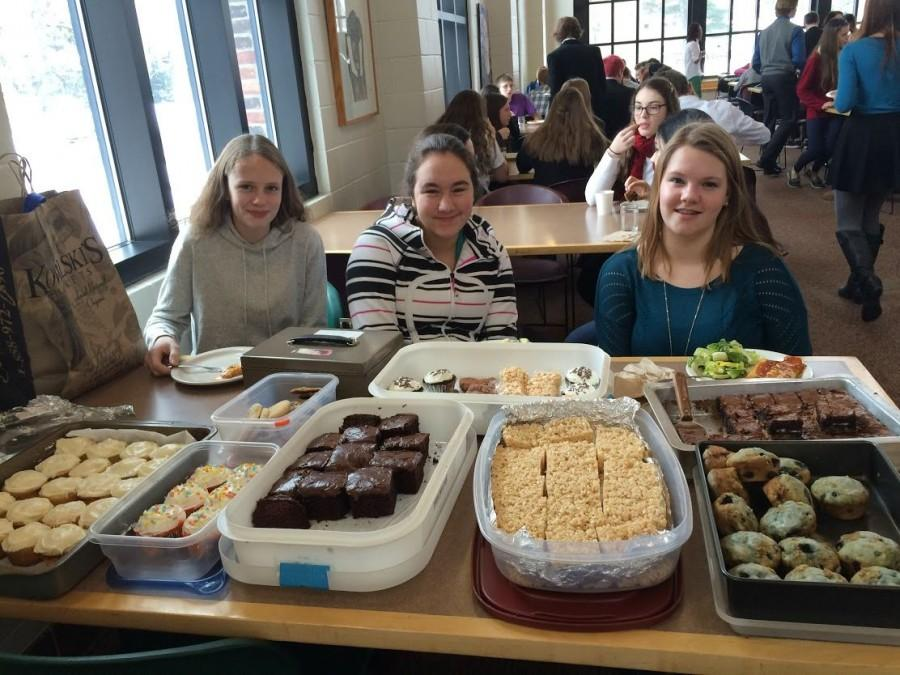 Sophomores+Mackenzie+Kuller%2C+Shelby+Tietel%2C+and+Samantha+Bluhm+work+at+the+bake+sale+to+raise+funds+for+Heifer+International+during+their+lunch+period.+