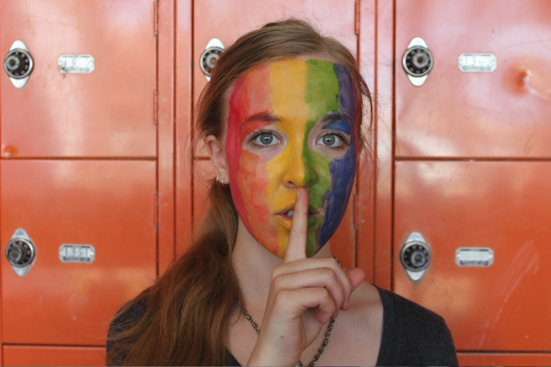 """Junior Miriam Tibbetts poses for the National Day of Silence on Apr. 17 with a finger over her mouth. This action symbolizes the quiet that is used to make a bigger sound. The face paint shows support for the LGBTQ+ community. """"It's important to use Day of Silence to pay tribute to those who have been silenced, to help show people they aren't alone in feeling silenced, and encourage change to help people regain their voices,"""" senior GSA Co-President Maggie Clark said."""