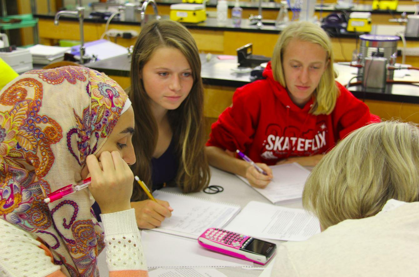 Sophomores Iya Abdulkarim, Emily Carter and Emma Hills work on problems in Honors Chemistry.