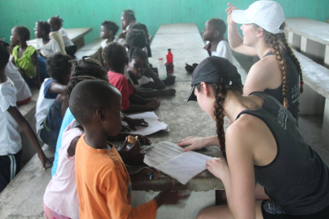 Freshman Mimi Geller and sophomore Greta Sirek sit and read with school kids through the Haitian Initiative. Unlike mission-related trips, Haitian Initiative is a non-denominational program.