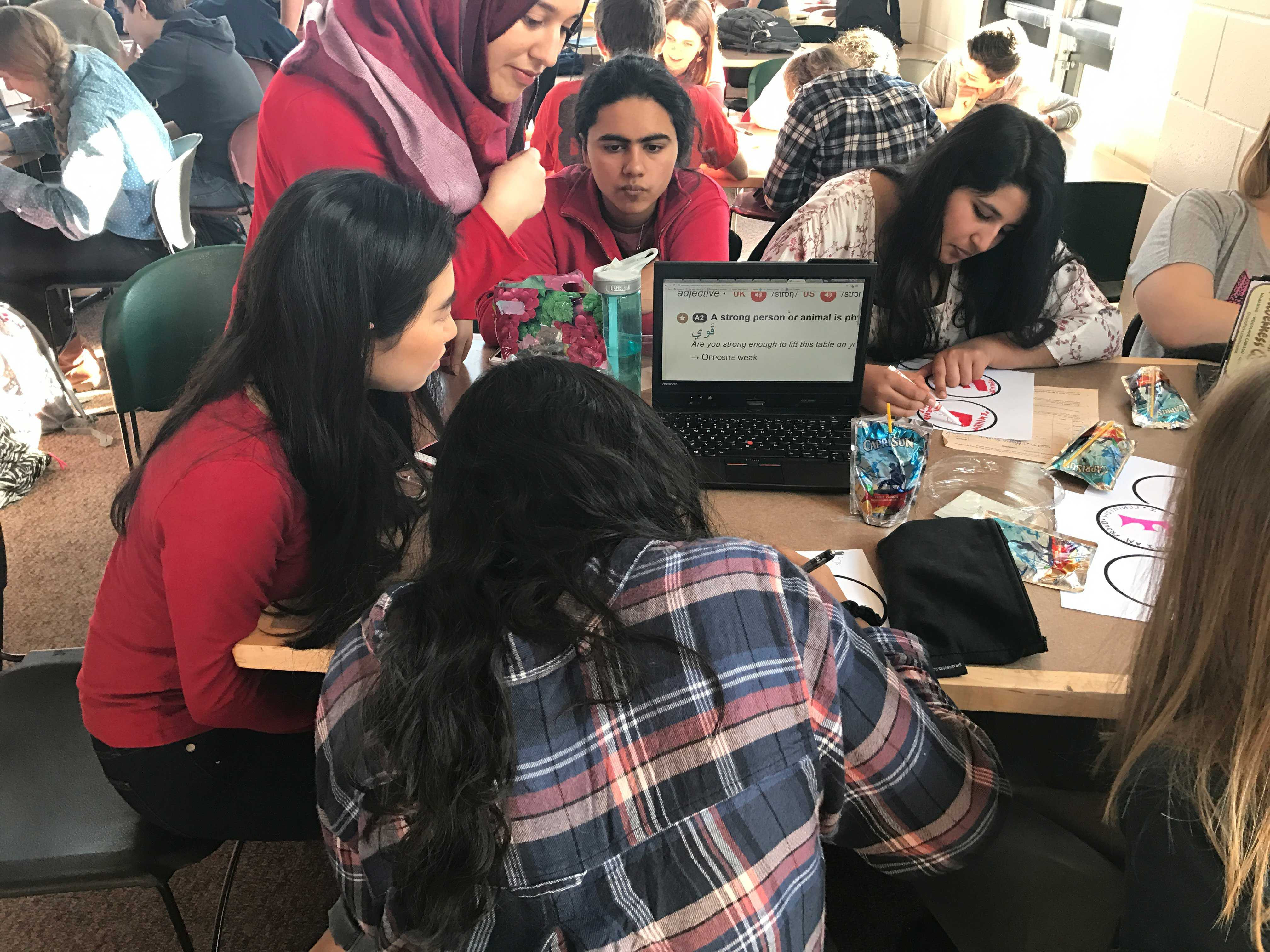 Seniors Amodhya Samarakoon, Stephanie Li, Noor Quiereshy, Sarah Murad, and Tabeer Naqvi work on their feminist stickers.