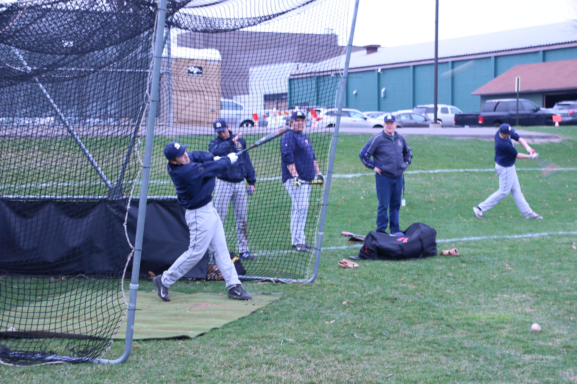 Senior captain Riley Bowman practices hitting baseballs in the batting cage.