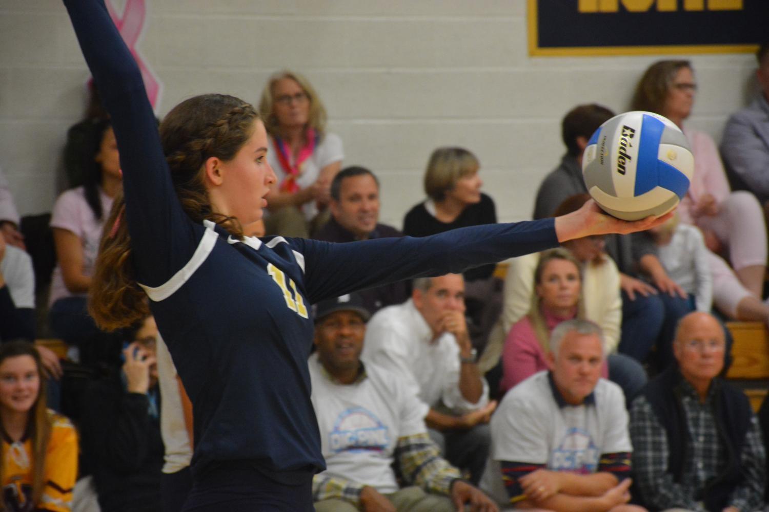 Junior Blythe Rients prepares to serve during a volleyball game.