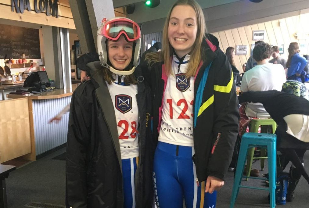 """Ladenburger and ninth grader Julia Scott buckle up before they head out to an Alpine race. """"I like painting class, which isn't really an academic class but I think it's fun. I also do skiing, and I like doing that through the school here,"""" Ladenburger said."""