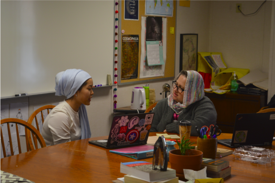 US+history+teacher+Molly+Ward+and+junior+Elea+Besse+go+over+her+history+agenda+in+a+hijab.+This+is+the+third+annual+Hijab+Day+organized+by+the+Muslim+Student+Alliance.