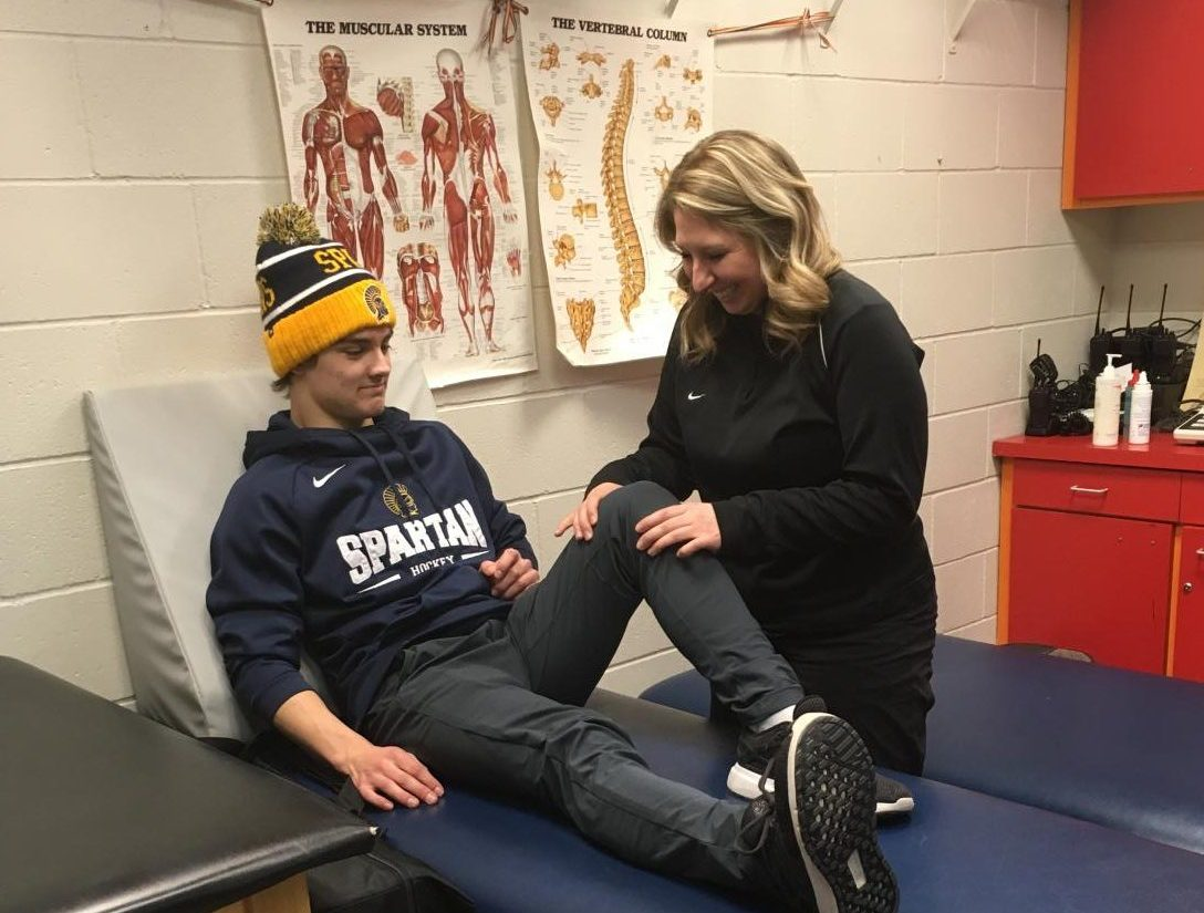 HOLD STILL. Upper School athletic trainer Lauren Kijewski tends to a student.
