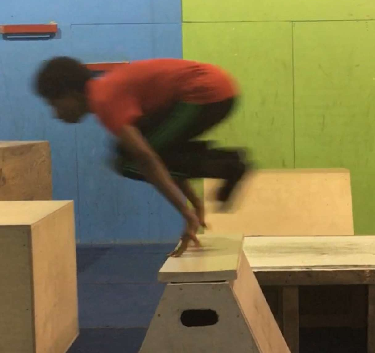 Junior Imran leaps across an obstacle as he freeruns across a parkour course.