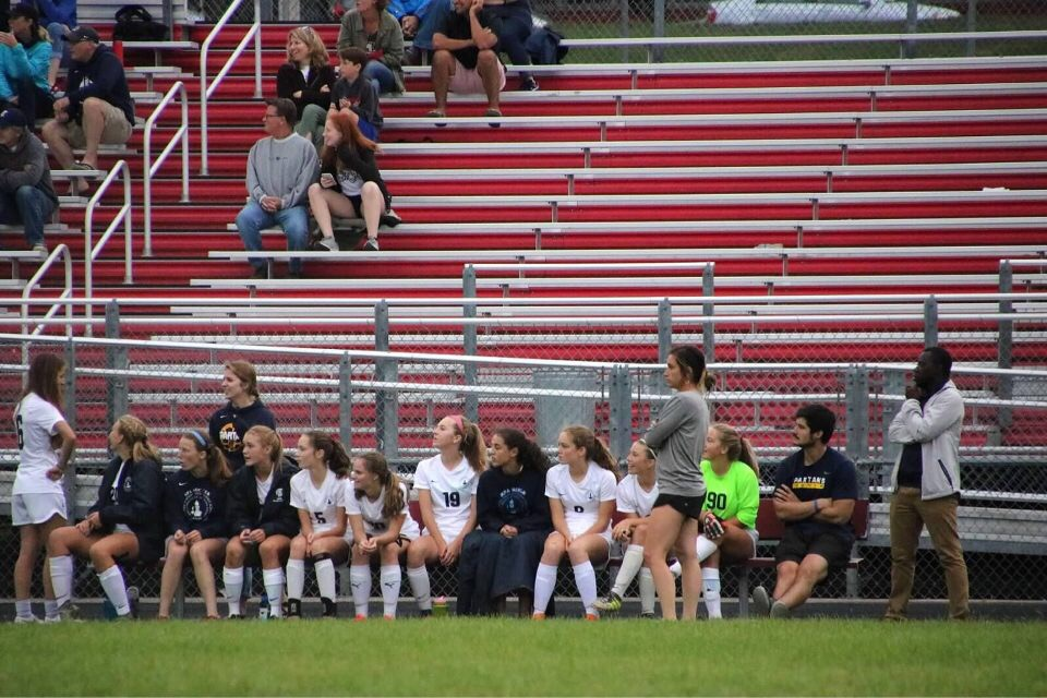 Girls varsity soccer manager Gabby Harmoning stands with her team.
