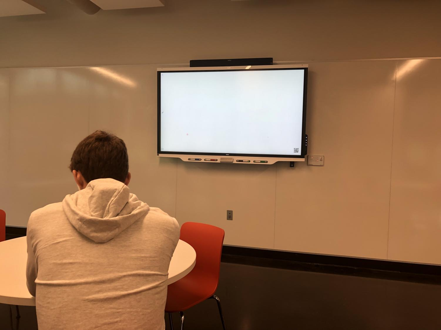 Senior Will Christakos studies in the Schilling Center in front of an unused smartboard.