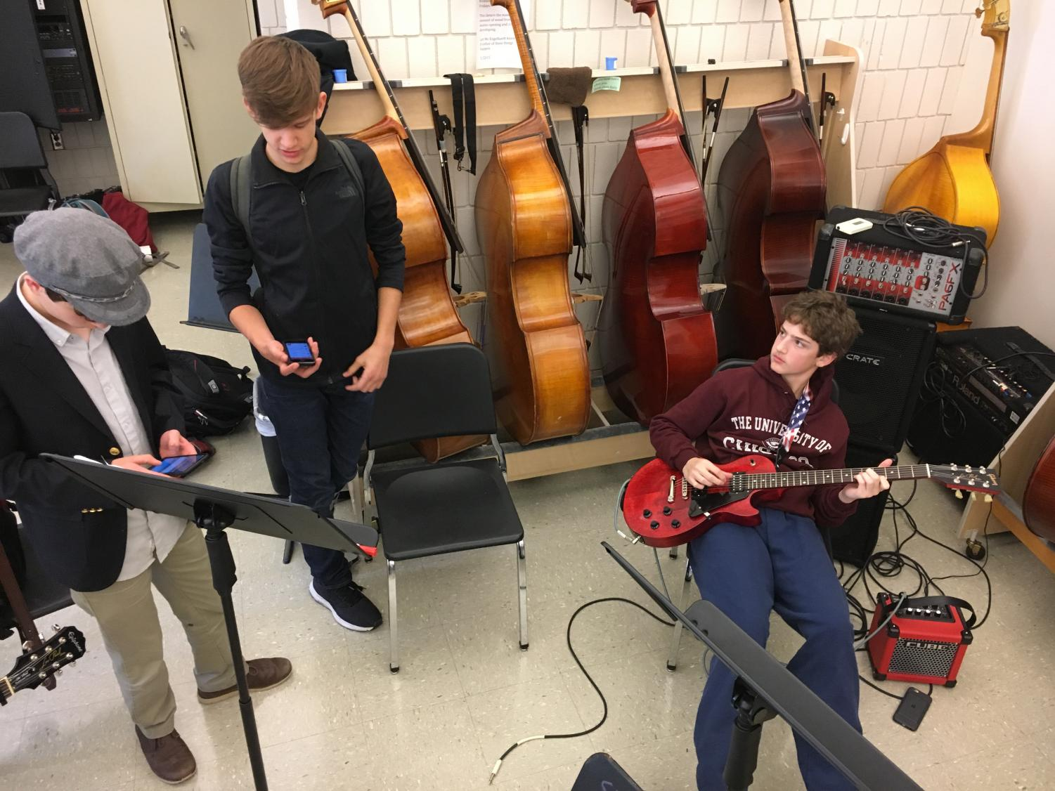 Ninth graders Henry Burkhardt and Nathan Mann, and sophomore Sam Konstan warm up before their band practices.
