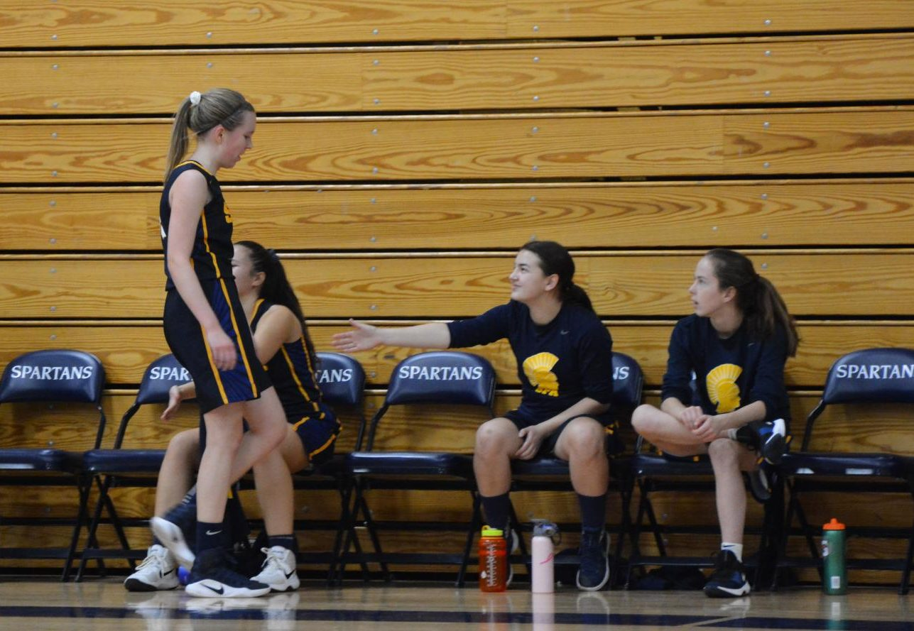 Junior Abby Hedberg is greeted with words of encouragement from her teammates as she comes off the court.