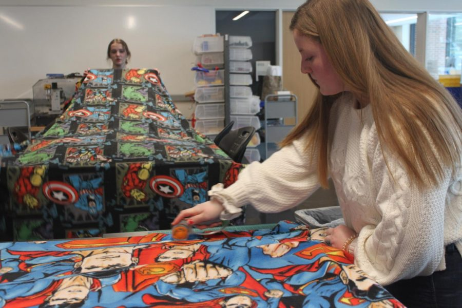 CAS+president+and+senior+Ellie+Nowakowski+cuts+pieces+of+fleece+blanket+with+help+of+CAS+members.