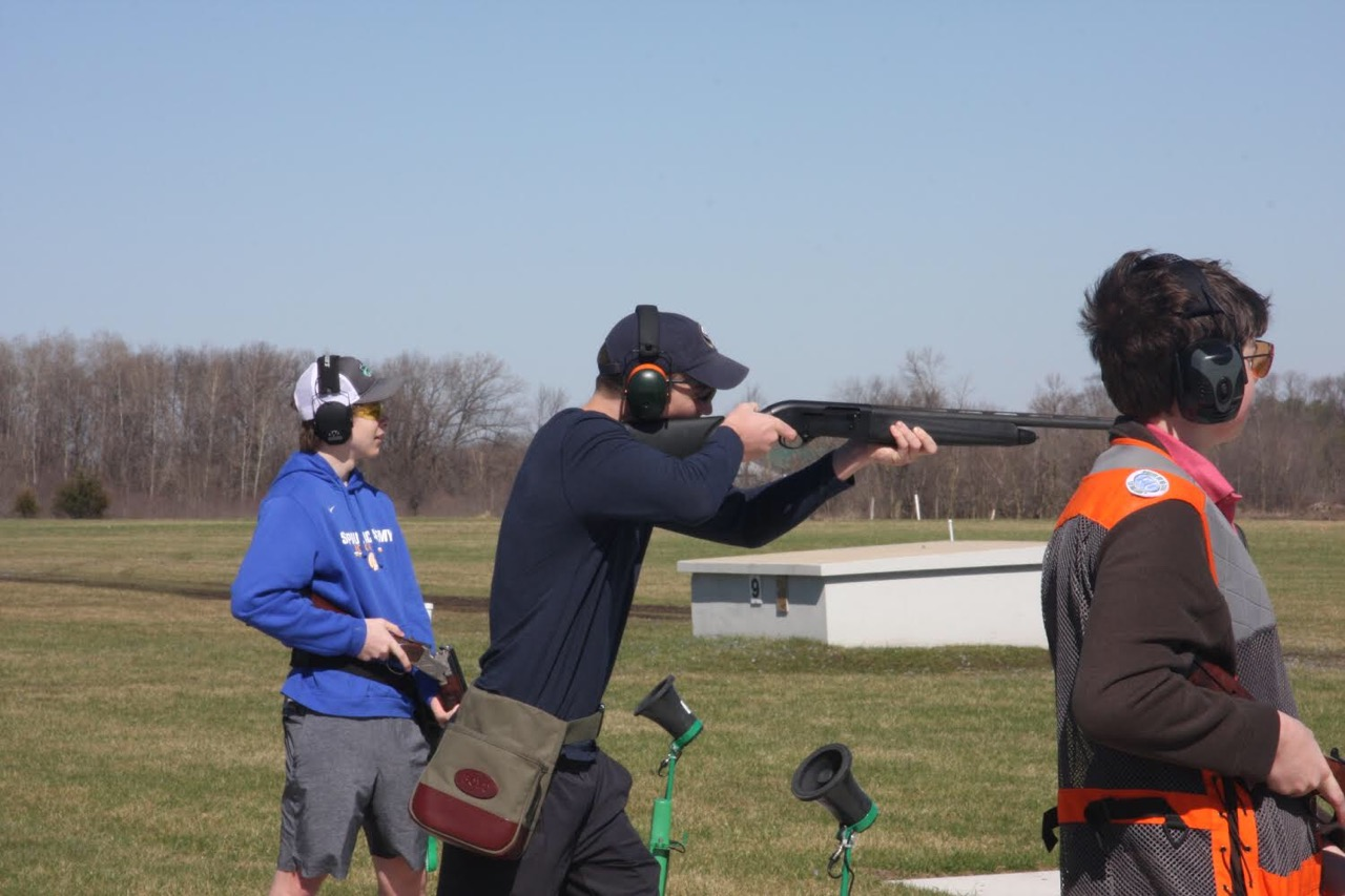 Junior Eric Bottern (middle) aims for a clay pigeon in his first round of the day.
