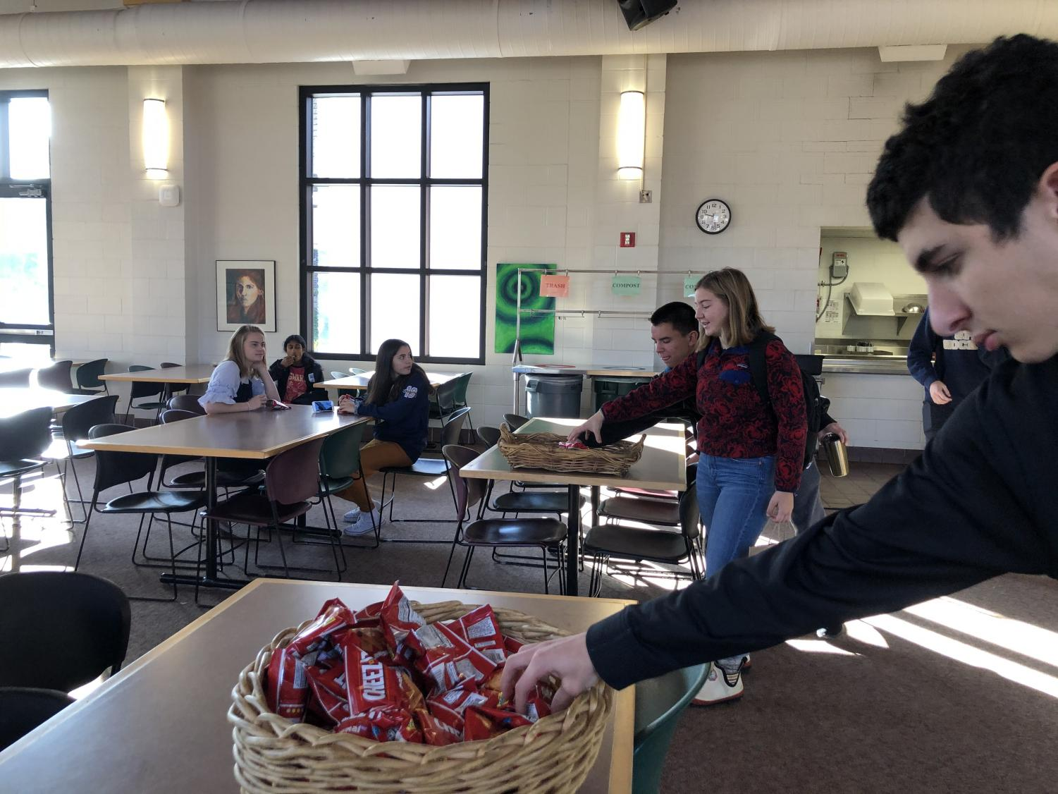 Seniors Stevie Frisch and Pia Schultz and junior Gabe Ramirez grab snack. The new setup features multiple snack baskets at tables in the cafeteria.