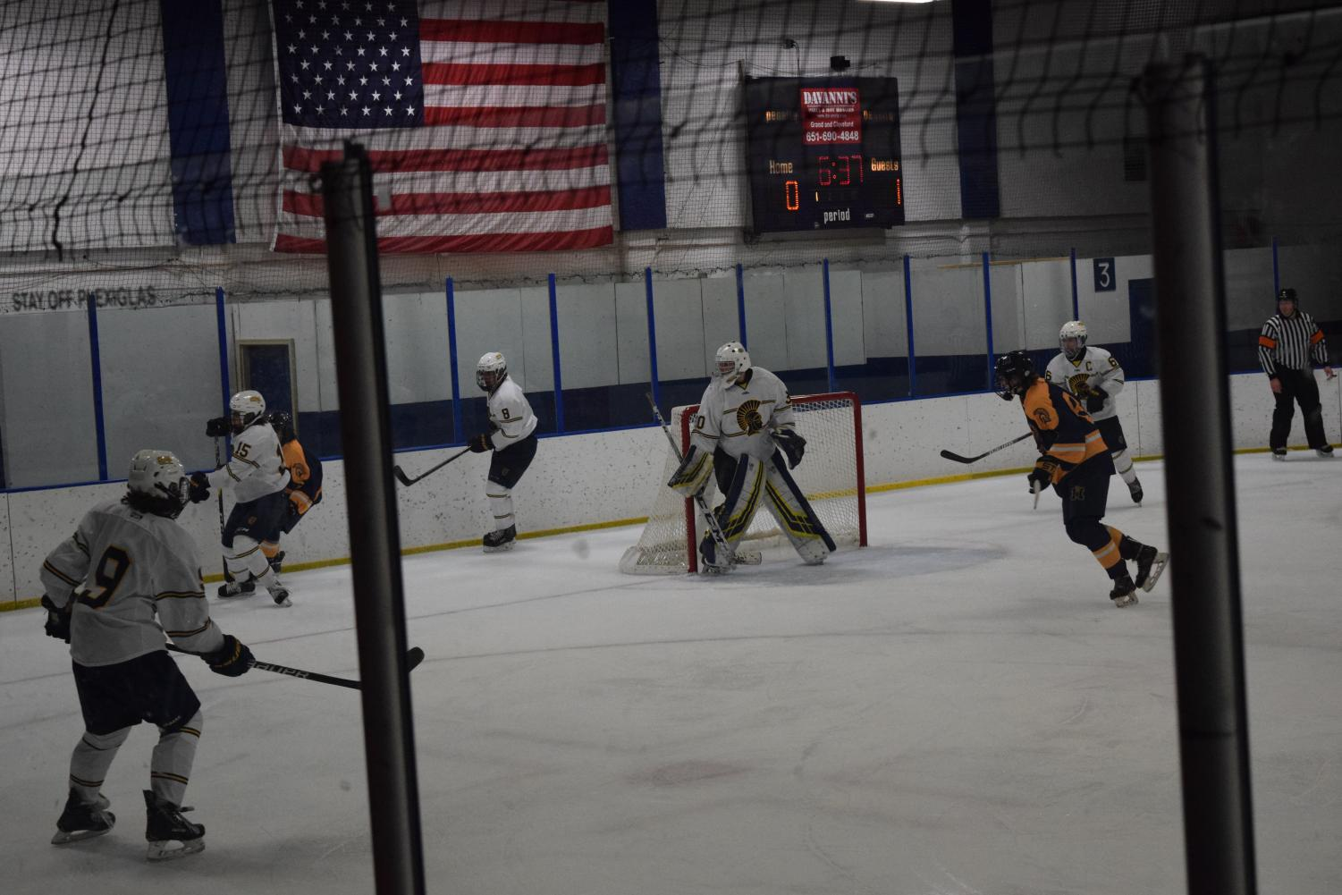 Senior Goalie Tom Kuriscak remains alert in the net while Junior Will Schavee battles at Mahtomedi player.