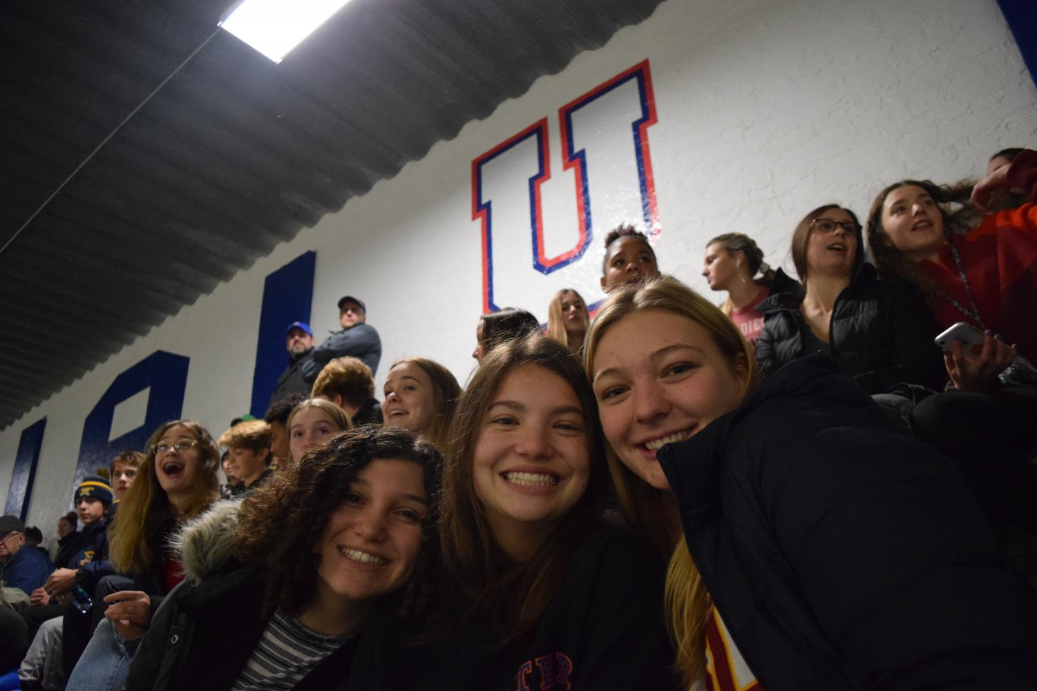 While a large number of fans can be a rare occurrence at sporting events, lots of students turned out to the Dec. 5 hockey game vs. rival Mahtomedi, demonstrating the atmospheric change that student support can bring. Here, Seniors Libby Cohen, Issy Weber and Helen Bartlett are all smiles at the game.