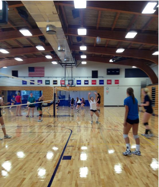 """The Girls Varsity Volleyball team practices on the new gym floor.  The gym is now more open to students during school hours. """"Being a basketball player, it's nice to get a couple shots up during the day, especially when I have a couple minutes here and there open in my schedule,"""" sophomore Kent Hanson said."""