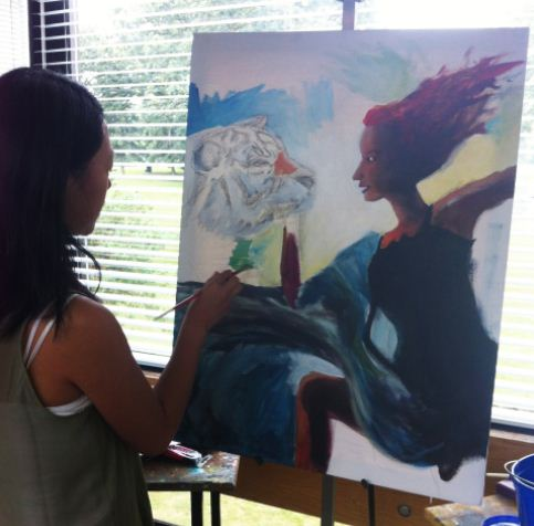"""Senior Alicia Zhang works on her latest painting. """"I've done it for so long that it kinda just became a habit… it's just part of what I do,"""" she said."""