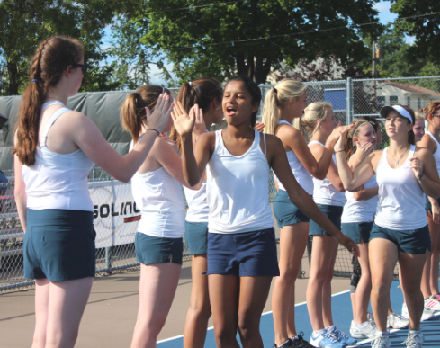 """Doubles  partners senior Aria Bryan and sophomore Ella Hommeyer get high-fives from their teammates before a match against St. Anthony Village High School on  Sept. 12. """"We work really well together, everybody gets along really well, and we all have really good sportsmanship which is awesome,"""" senior captain Alida Mitau said."""