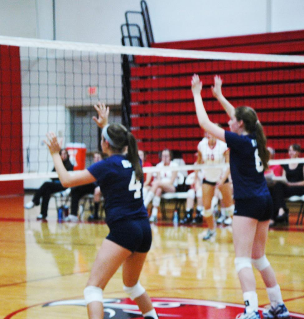 """From left: Junior captain and outside hitter Mira Grinsfelder and senior captain and middle hitter Claire Foussard are in the ready stance in a match against Minnehaha Academy on  Sept. 16. """"I think this season will be a huge improvement over seasons before,"""" Grinsfelder said."""