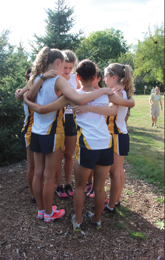 """From left: Junior captains Ellen McCarthy and Mary Naas, and eighth grader Val Hart, freshman Neeti Kulkarni, and eighth grader Greta Sirek visualize before their race at St. Catherine University on Sept. 12. """"We lost about four seniors total, who were important contributors to the team, but we have some really good younger runners who are really growing into the team,"""" junior captain Ellen McCarthy said."""