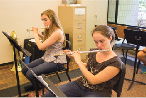 """Senior Claire Foussard and sophomore Maya Smith  play flutes in a winds sectional class. """"I don't really like how we have to do more stuff during tutorial, but I don't think it's that bad,""""  senior Alex Miller said."""