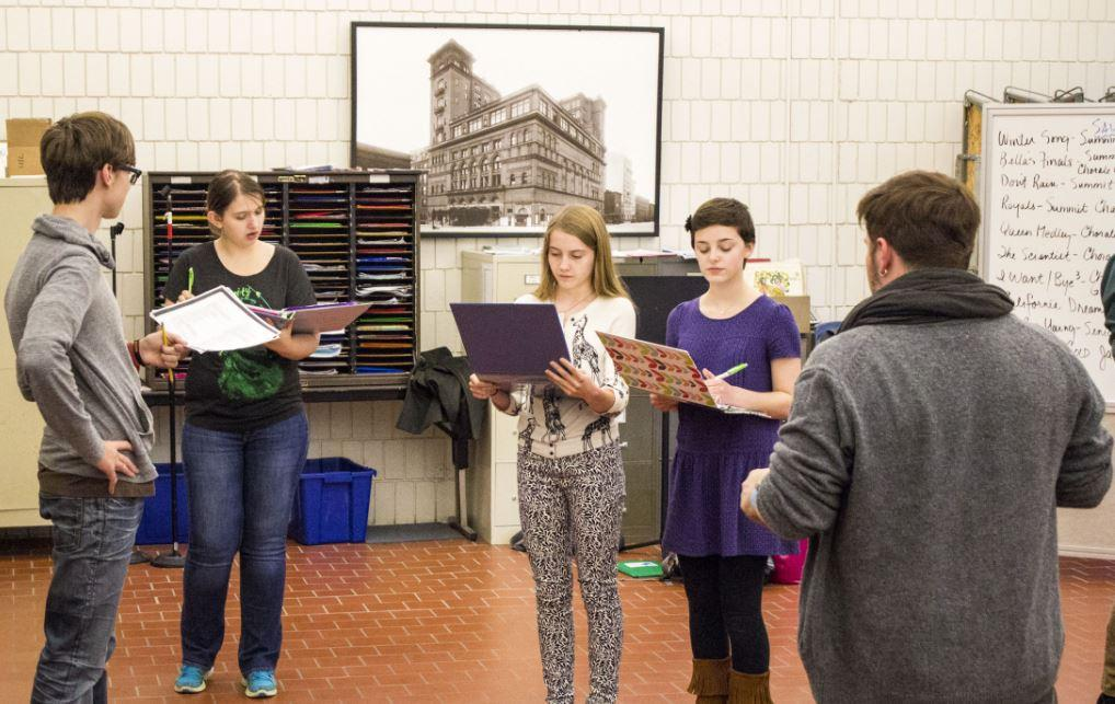 """From left to right, freshman Henry Ziemer, senior Emily Ross, sophomore Anna Biggs, sophomore Maggie Vlietstra and Upper School theater director Eric Severson work on blocking for the fall play. """"The play requires a very large cast… Some actors are cast in multiple roles,"""" Severson said."""
