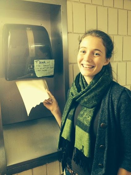 """People for Environmental Protection president senior Charlotte Hughes poses with a paper towel dispenser labeled with one of PEP's signs. """"We try to get creative with our projects and announcements, so why not the signs too?"""" Hughes said."""