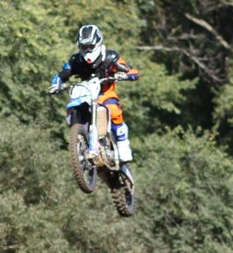 """Junior Nicolas Koch performs a jump on a motocross bike. """"[A friend] invited me to come try it one day and let me borrow his bike, and I got hooked on it,"""" Koch said."""