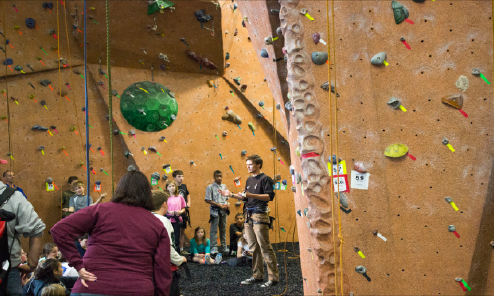 "An instructor at Vertical Endeavors in St. Paul, the indoor rock climbing facility where freshman John Connelly practices, speaks to a group of children about youth programs. ""What people don't always realize is there's a lot of strategy around [rock climbing],"" Connelly said."