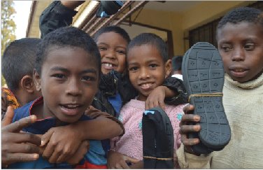 """Children in Madagascar pose with their new TOMS® shoes, courtesy of the One for One program. """"I think TOMS® are awesome. It's nice to know there's kids somewhere else looking stylish,"""" senior Frank Nahurski said."""