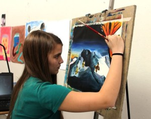 Sophomore Michelle Heilig works on a surrealist painting in the art wing.