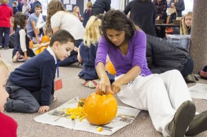 Senior Aria Bryan helps her kindergarten partner carve into his pumpkin.