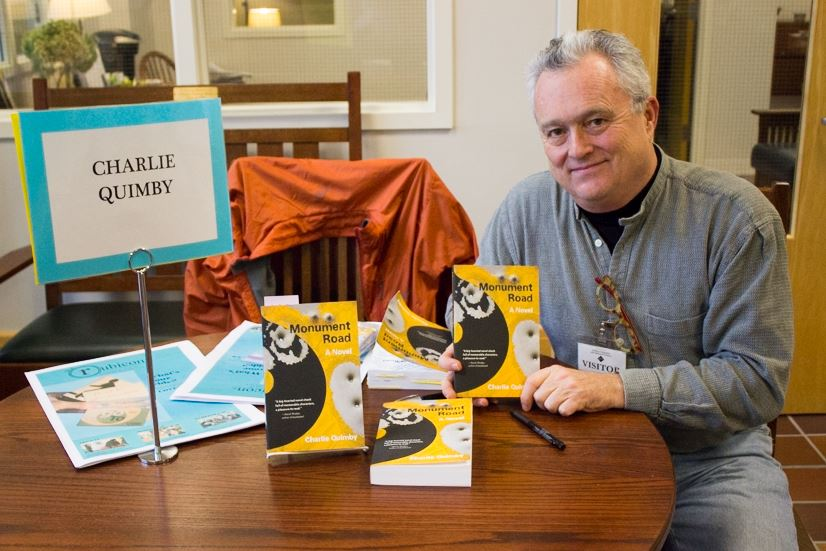 Author Charlie Quimby sits at his book signing table in the Summit Center on Nov. 20.