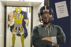 Football captain senior Sam Carlson poses in front of the boys locker room.