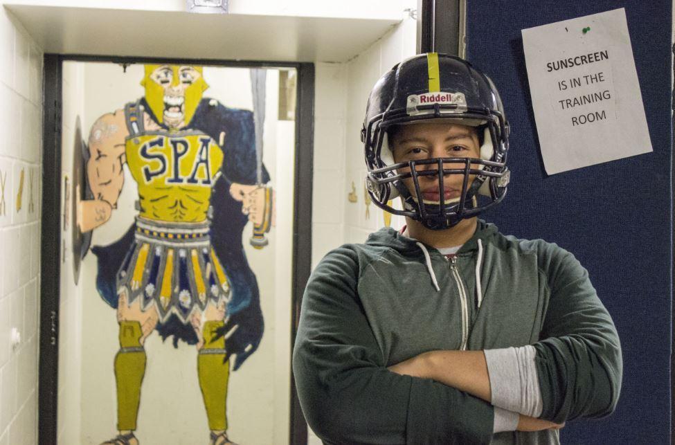 Football captain senior Sam Carlson poses in front of the boys locker room.