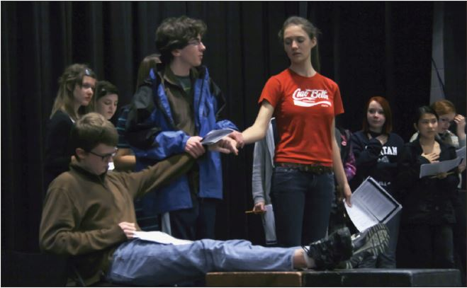 """Freshman Cole Thompson, junior Halsey Moe (sitting) and senior Charlotte Hughes rehearse a wedding scene from The Caucasion Chalk Circle. """"The cast has been absolutely phenomenal,"""" Upper School theater director Eric Severson said."""
