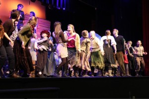 "The cast of The Caucasian Chalk Circle warms up onstage by dancing to music. ""Warm ups, for what we do, is to get everyone pumped up and energized,"" junior Sophia Harrison said. ""It gets us kind of in the mode. It's kind of like a wake-up call, like 'it's show time!""' she added."