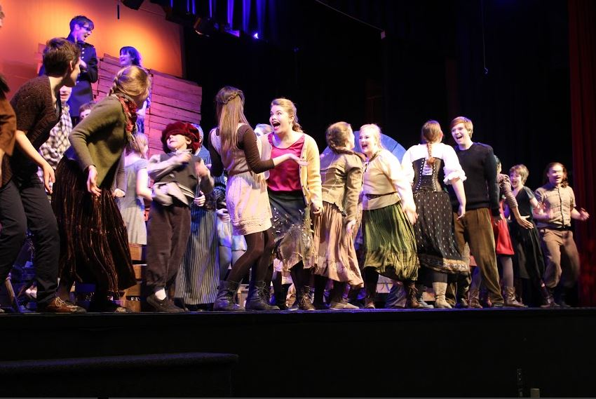 """The cast of The Caucasian Chalk Circle warms up onstage by dancing to music. """"Warm ups, for what we do, is to get everyone pumped up and energized,"""" junior Sophia Harrison said. """"It gets us kind of in the mode. It's kind of like a wake-up call, like 'it's show time!""""' she added."""