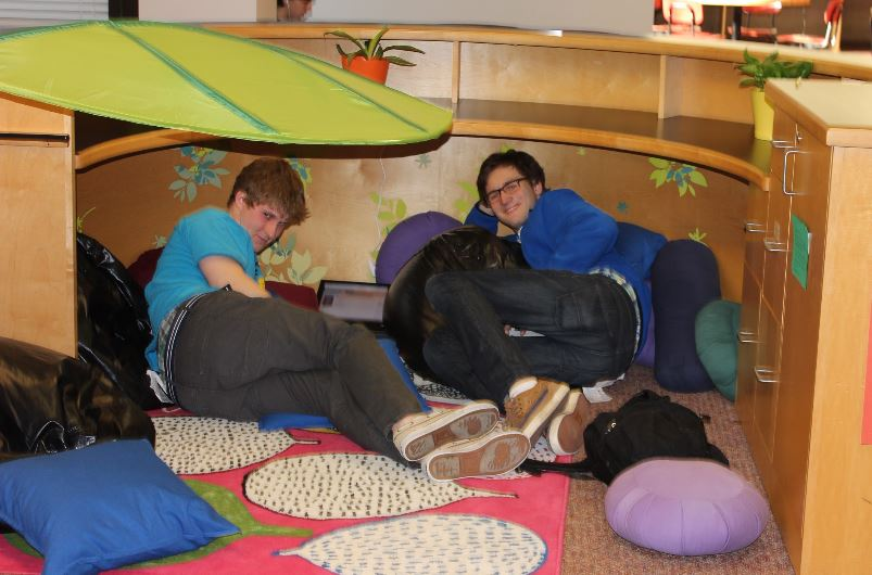 """Seniors Jonathan Sogin and Connor Allen relax in the library. """"I think what we're really missing now is a chimpanzee,"""" Allen suggested. """"If we could just have a chimpanzee to cuddle with, that would be prime."""""""