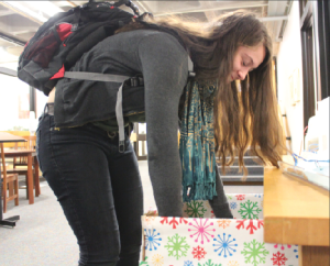 "Junior Julia Lagos adds toys to the Toys for Tots drop box outside the Dean's Office. "" [Adopt a Family] was just a lot of work to do around the holidays with so much to do already,"" senior Aria Bryan said. ""So we thought that Toys for Tots would be a good substitution."""