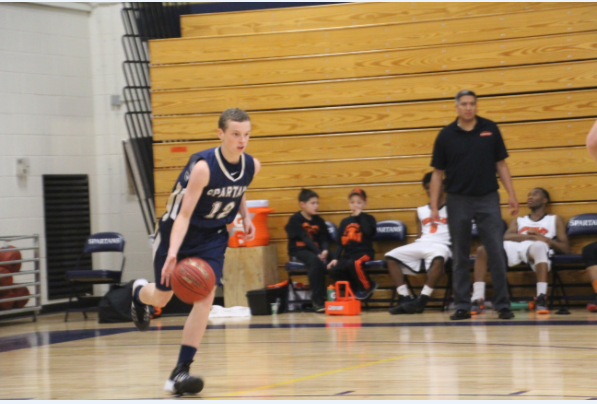 Sophomore Charlie Hooley brings the ball up the court in the team's Nov. 26 game against St. Paul Humbolt High School. The Spartans beat the Hawks 83-58.