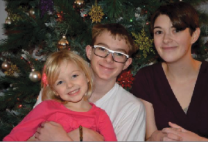 "Senior Victoria Guest (far right) poses with younger siblings Cameron Guest (center) and Olivia Campbell (left) in front of their 2013 Christmas tree.  ""We decorate with silver and frosted glass balls and glittery snowflakes that are purple, pink, turquoise, and green,"" Guest said."
