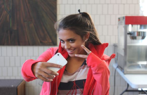 """Sophomore Sami Brattland snaps a selfie with her phone. """"It's constantly about you, you, you, you, you,"""" junior Kailey Wendlandt said."""