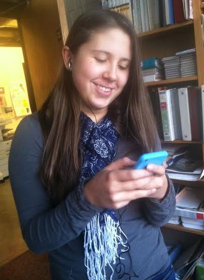 """Senior Anna Matenaer looks up songs on her phone. """"I think that Imagine Dragons should win Record of the Year [at the 56th Annual Grammy Awards],"""" she said"""