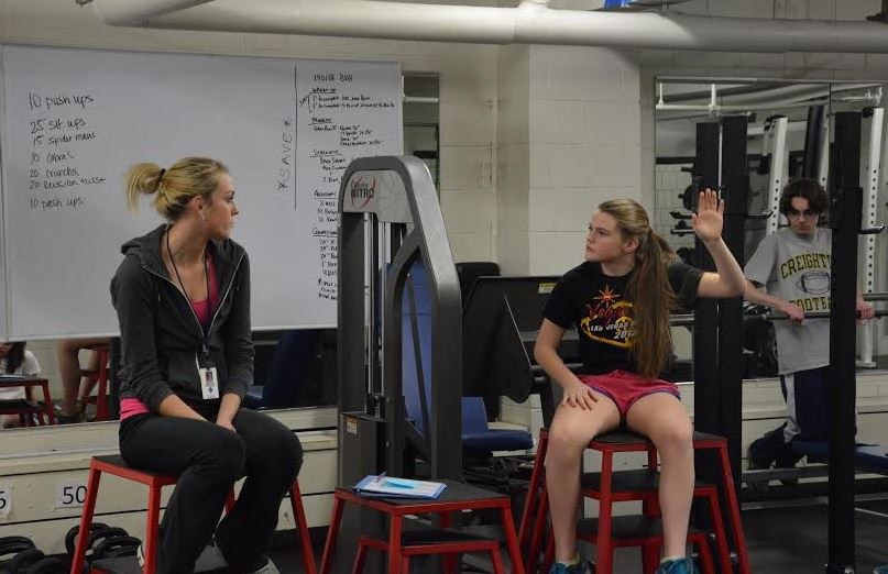 """Freshman Lauren Hansen and freshman Cole Thompson attend Fitness for Life, taught by  Kaitlyn Frenchick (on left).  """"I discuss what you should have in every meal, roughly how many calories you should have every day, and just understanding what a balanced diet and good eating habits are,"""" Frenchick said."""