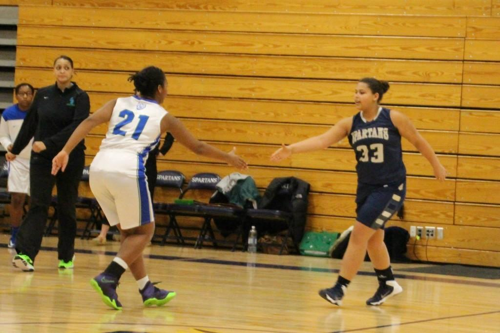 """Senior Girls' Basketball captain Jonte Claiborne shakes hands with an opponent of Blake prior to the team's Jan. 30 game. """"Nobody wants to lose a conference game-- especially to someone who is as big of a rival as Blake is to us,"""" junior basketball player  Katie Ademite said."""