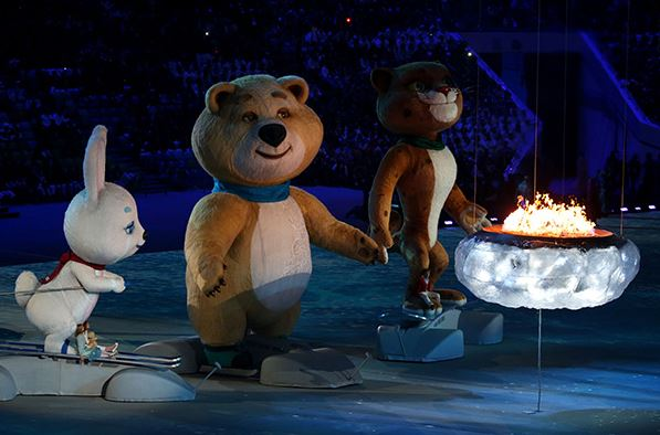 The mascots of the 2014 Winter Olympics arrive on stage to blow out the Olympic flame.