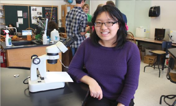 """Li poses in her science classroom. """"I was looking for the most environmentally friendly way of doing things. Making biofuels from switchgrass is actually carbon negative, and since everything around us is so carbon positive, it's good to have something which can help mitigate the effects of climate change,"""" Li said."""