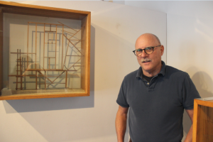 """Upper School Fine Arts teacher Bob Jewett stands by his artwork in his show at Drake Gallery. """"I think working clay is so much fun, that it'd be hard for someone to not experience that kind of satisfaction and joy of pulling the clay,"""" Jewett said."""